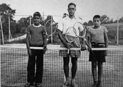 Années '50. On jouait au tennis sur les terrains où on joue au basket-ball présentement. Notez les raquette en bois.