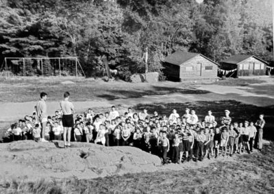 Années '50. Rassemblent sur la roche avec le chef de camp Gaston Lapointe. Notez les balançoires. On aperçoit un bâtiment à coté de la cabine 10 qui fut déménagé pour devenir la Ruche.