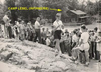 """Autour de 1951. Distribution du courrier à la roche de la cantine. Le camp Lebel  était une """"grosse cabine"""" qui servait à loger des campeurs. Il fut démoli autour de 1953. Il fut nommé en l'honneur du premier directeur du camp en 1938."""