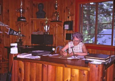 """Années '60. Valencia Marcoux qui fut la secrétaire du camp de 1943 à 1979. Notez le téléphone au mur qui datait de la deuxième guerre et qui servait de communication entre les différents bâtiment. On tournait une manivelle et on signalait par ex. le Foyer """"un grand, deux petits coups""""."""