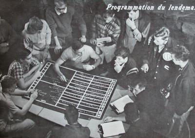 Autour du 1961. Le staff se réunit en soirée pour la programmation du lendemain. La majorité fumait.