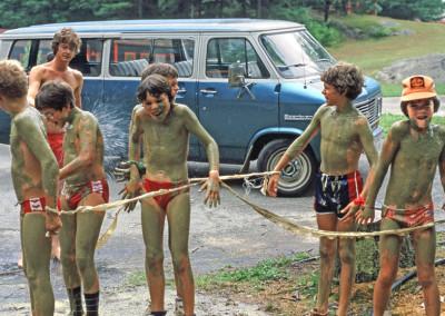 1980. Le grand-Jeu des autos de courses. Arrêt à la station de lavage. On aperçoit le campeur Jacques Boulanger (lunettes) se faisant arroser. Il devint président de la corporation du camp autour des années 2010