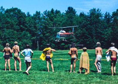 1981. Un père de campeur fait une visite au camp en hélicoptère. Il nous prête son hélicoptère - et son pilote- pour faire des photos aériennes du camp.